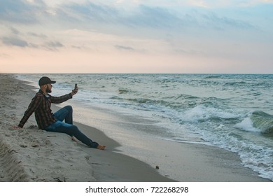 Young man with his morning cup of coffee looking to the ocean view