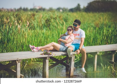 Young man and his pregnant wife spending time on nature