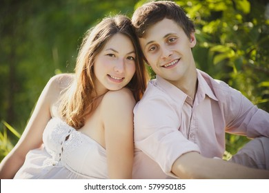 A young man with his pregnant wife sitting on the grass in the park near the lake in summer