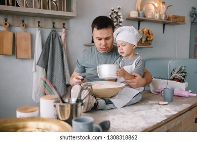 Young man and his son with oven sheet in kitchen. Father with little son on the kitchen