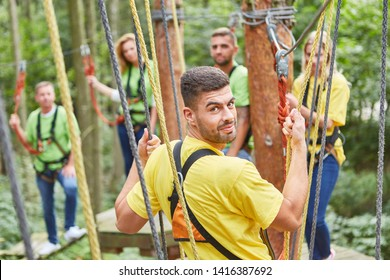 Young man and his team together in high ropes course at teambuilding event