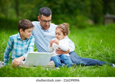 Young man and his two children sitting on grass in the park