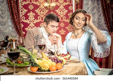 young man in a historic jacket and girl in vintage dress sitting at the richly laid table in a restaurant. Elegant vintage couple in restaurant. Retro couple portrait. Romantic Beauty.Vintage Styled