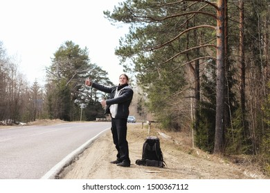 A young man is hitchhiking around the country. The man is trying to catch a passing car for traveling. The man with the backpack went hitchhiking to south.