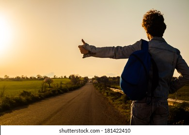 Young Man Hitchhiking on a Country Road