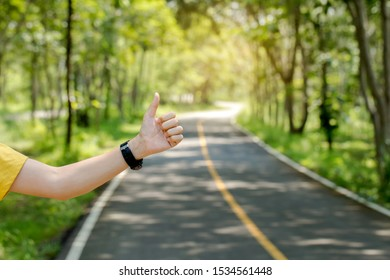 Young man hitchhiking on a road