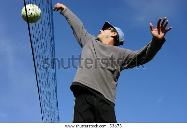 Young man hitting the ball over the net