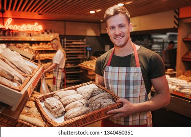 Young man hold basket of fresh tasty bread in hands. At grocery store. Guy look on camera and smile. Positive happy worker in store.