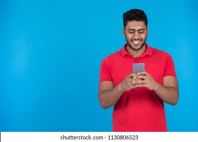Young man hold his phone and typing, chatting with friends smiling, on a blue background.