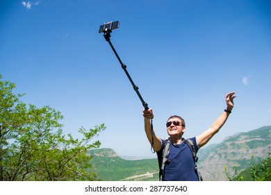 Young man hold monopod in hand taking selfie on mobile phone. Summer vacation.Countryside hiking. Happy backpacker tourist. Explore world travel. Freedom life.Copy space. Active lifestyle. Armenia