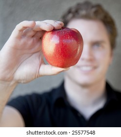 A young man is holding an apple up to his eye with the apple covering some of his face in front of his eye