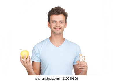 young man holding apple on white. guy holding pack of cigarettes in one hand isolated on white background