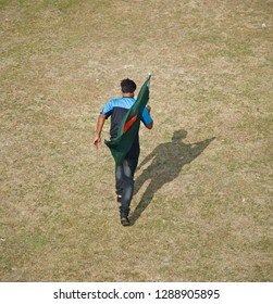 Young man holding a Bangladeshi flag running around a field