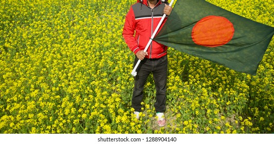 Young man holding Bangladeshi national flag standing around a mustard field