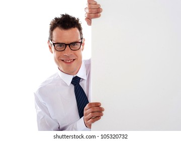 Young man holding a big white blank  signboard and looking at camera