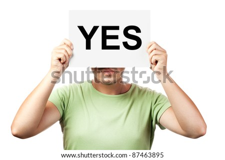 "young man holding a billboard with word ""yes"" isolated on white background"