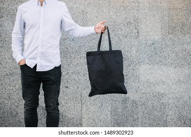 Young man holding black textile eco bag against urban city background. . Ecology or environment protection concept. Black eco bag for mock up
