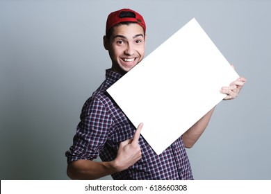 Young man holding a blank paper in a studio