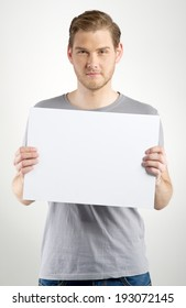 Young man holding blank sign in hands