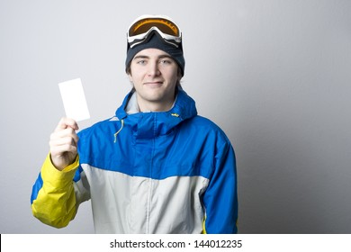 Young man holding blank ski lift pass looking. Concept to illustrate ski admission fee
