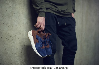 Young man holding blue Nike Air Huarache sport shoes shot on grey background. Nike sneakers, trainers close up view. Sport and casual footwear concept. Krasnoyarsk, Russia - January 10, 2018