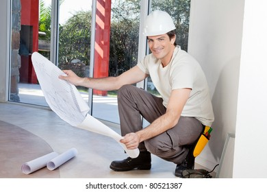 Young man holding blueprint and smiling