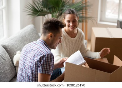 Young man holding book helping wife to pack cardboard boxes on moving day, smiling young couple unpacking sorting belongings settle in new home, family preparing for relocation together concept