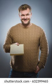 young man holding book and smiling on grey background