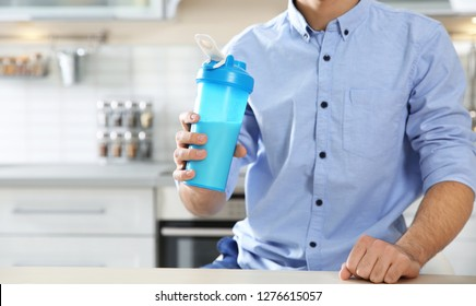 Young man holding bottle of protein shake in kitchen, closeup. Space for text