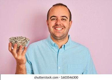Young man holding bowl with sunflowers seeds standing over isolated pink background with a happy face standing and smiling with a confident smile showing teeth
