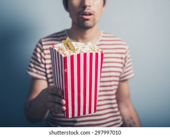 A young man is holding a box of popcorn with a cinema ticket in it