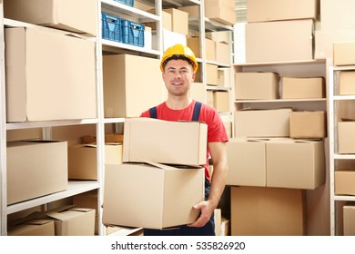 Young man holding boxes at warehouse