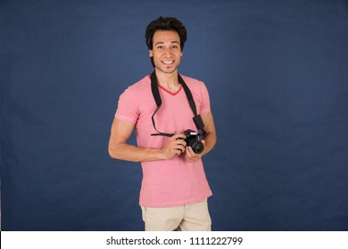 young man holding camera and taking photos while smiling to the camera , in a blue background
