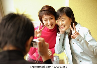Young man holding camera, two women posing for picture, making peace sign