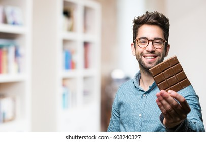 young man holding a chocolate bar