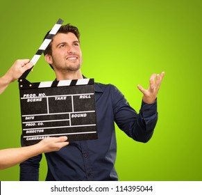 A Young Man Holding A Clapboard And Acting On White Background