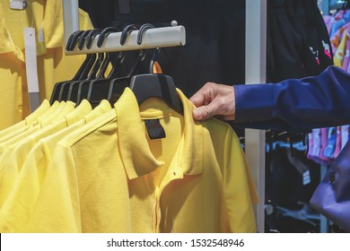 Young man holding coat hanger and checking polo shirt. Background with many  shirt hanging in closet. concept of buy, sell and clothes fashion