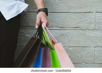 young man holding colorful shopping bag outdoors. shopaholic male standing beside gray wall. shopper enjoy buying. consumerism concept