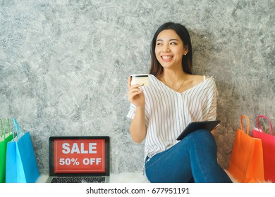 Young man holding credit card and using laptop computer. Online shopping concept