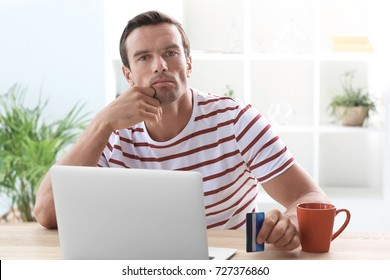 Young man holding credit card while using laptop at home