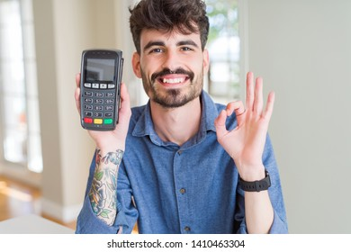 Young man holding dataphone point of sale as payment doing ok sign with fingers, excellent symbol