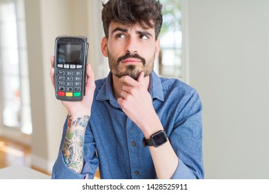 Young man holding dataphone point of sale as payment serious face thinking about question, very confused idea
