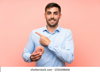 Young man holding a donut over isolated pink background pointing to the side to present a product