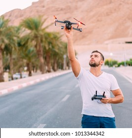 Young man holding drone before flight at nature. Pretty guy prepare to pilot outdoor