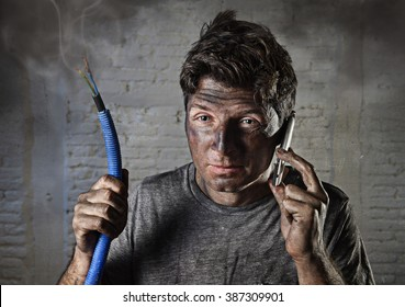young man holding electrical cable smoking after domestic accident with dirty burnt funny face expression calling desperate with mobile phone asking for help in electricity DIY wrong repairs concept