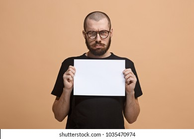 A young man holding an empty plate in his hands to fill your text. Emotional, courageous face. Isolated on pastel background. Copy space. Advertising and commercial design. Front view