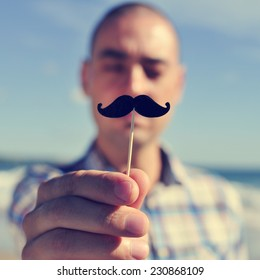 a young man holding a fake moustache in a stick in front of his face