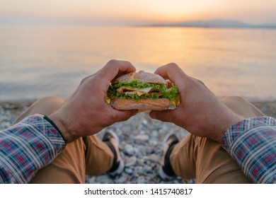 Young man holding fresh tasty burger and resting by the sea at summer sunset, point of view.