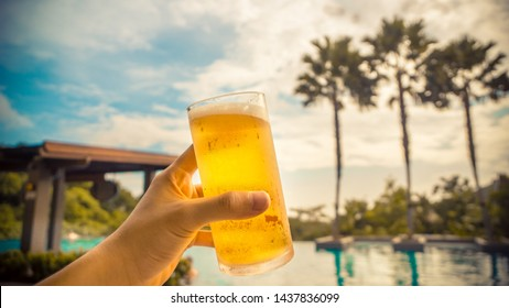Young man holding a glass of beer in his hand at the pool with a sunset mood and tropical palm trees in the background. (Summer, travel and vacation concept)
