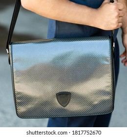 Young man holding a gray shiny messenger sport bag close up